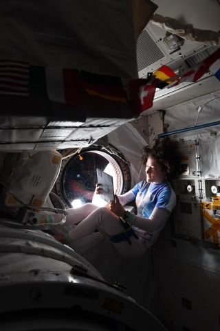 NASA astronaut Christina Koch relaxes by a window on the International Space Station to mark the U.S. Labor Day holiday on Sept. 2, 2019.