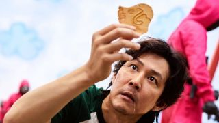 Gi-hun in Squid Game holding honeycomb candy