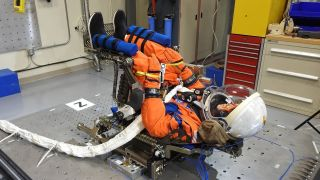 The 'moonikin' test dummy undergoes a vibrational test in a chair from the new Orion module at the Kennedy Space Center.