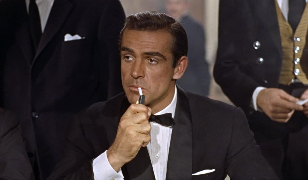 Dr. No Sean Connery lights a cigarette at a card table