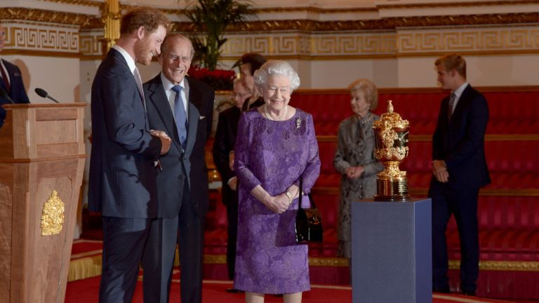 Prince Harry, Prince Philip, Duke of Edinburgh and Queen Elizabeth II look at the Webb Ellis Cup on a plinth during a Rugby World Cup reception at Buckingham Palace on October 12, 2015 in London.