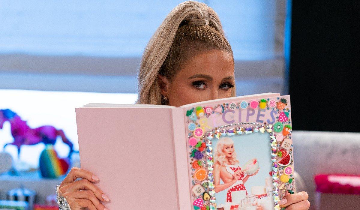 Paris Hilton hiding behind a book Cooking With Paris Netflix