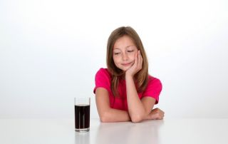 A girl looks at a glass full of cola.