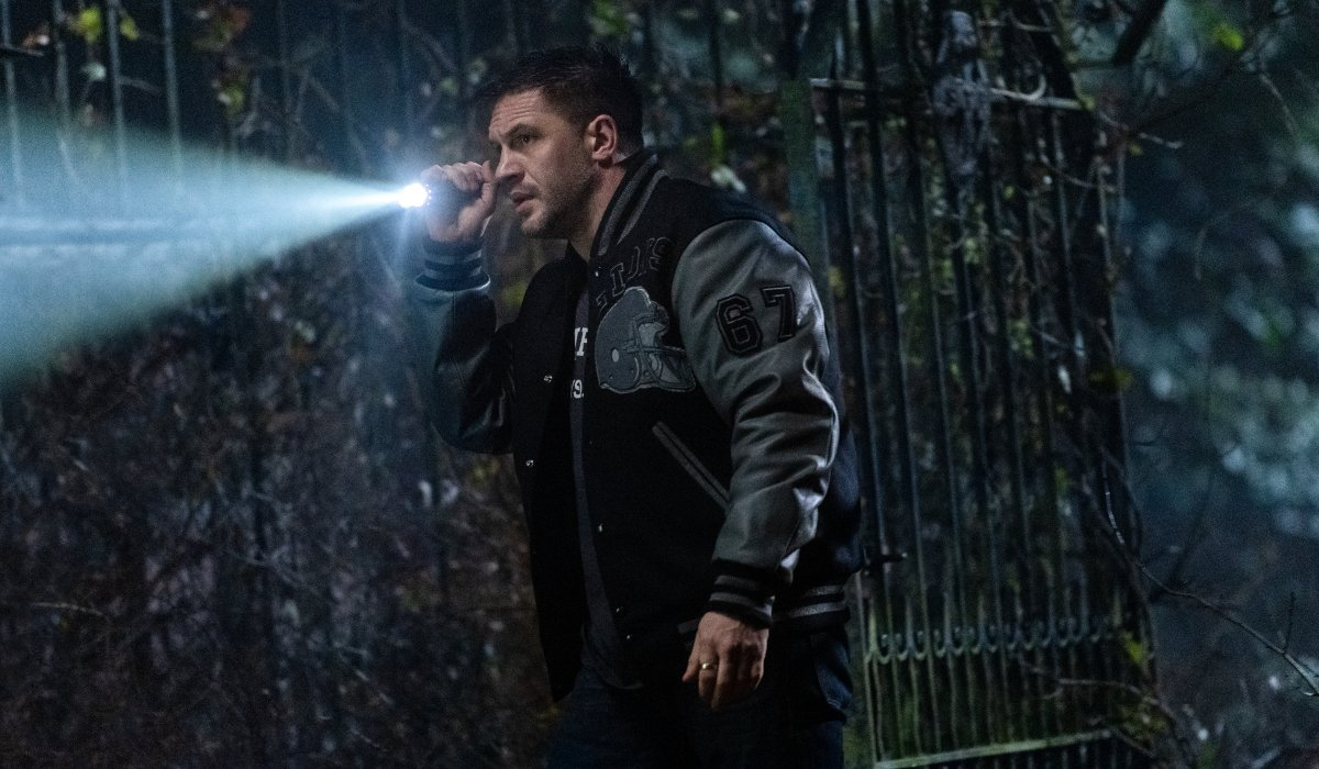 Tom Hardy investigates with a flashlight on a dark night in Venom: Let There Be Carnage.