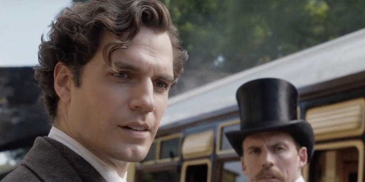 Sherlock (Henry Cavill) and Mycroft (Sam Claflin) stand outside of a train in Enola Holmes