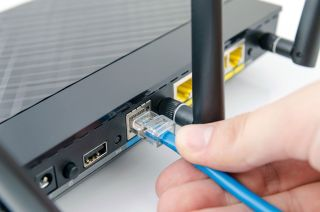 Hand plugging cable into a router Ethernet jack.