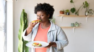 A woman at home eating a healthy breakfast of toast with avocado and tomato.