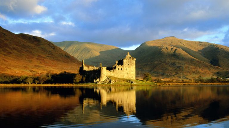 A photo of one of the castles in Scotland set against a Loch with mountains behind