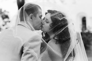 Bride and groom kiss under the veil.