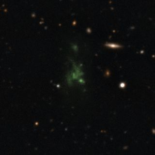 "A giant green ""space blob"" - called the Lyman-alpha blob LAB-1 - is seen in this composite of two different images taken by the Very Large Telescope in Chile. The LAB-1 space blob is 300,000 light-years across, making it one of the largest known single ob"