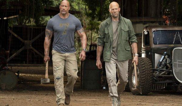 Hobbs and Shaw heading out of the Hobbs garage, weapons in hand