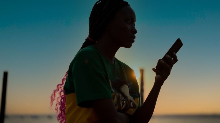 A profile shot of a young woman on a beach using her smartphone, the image is a silhouette as she is standing against a moody sunset