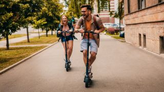 Young man and woman riding electric scooters