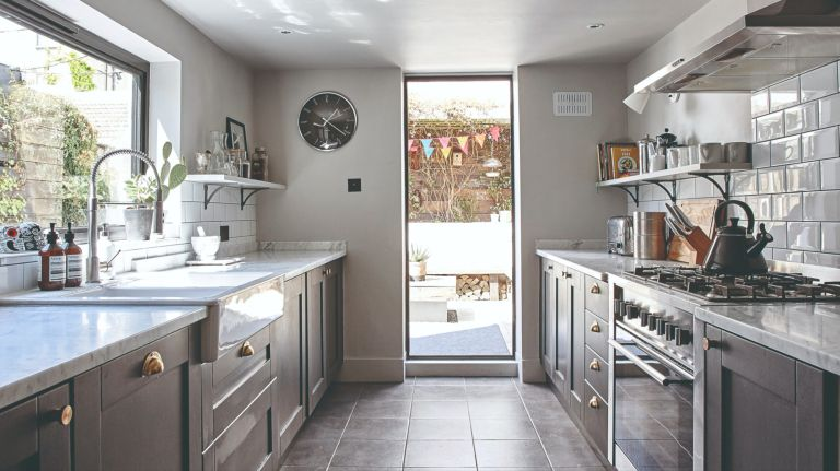 Galley kitchen with dark Shaker units, dark slate floor tiles and ceiling-to-floor picture window