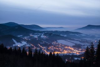 Landscape photo of a village at nighttime in winter.