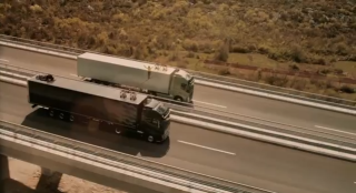 Faith Dickey slacklining between two semi-trucks on a Croatian highway.
