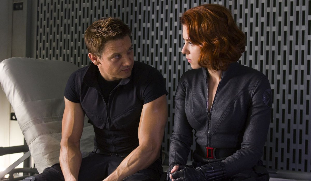 Jeremy Renner and Scarlett Johansson sitting on a cot, talking, in The Avengers.