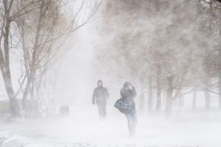 People walking through snow and wind.