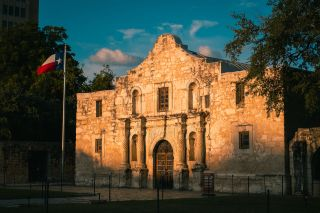 The Alamo at sunrise with the Texas flag waving.