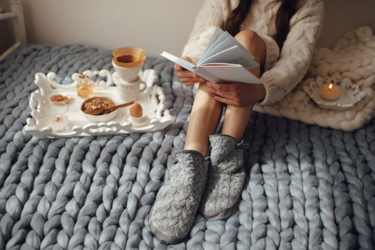Woman with long hair drinking hot coffee and reading book in bed. Woman in woolen socks and sweater sitting on wool chunky merino plaid.