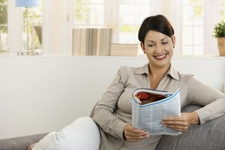 A woman reads a magazine.