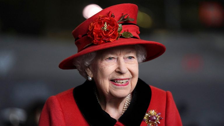 The Queen smiles in red