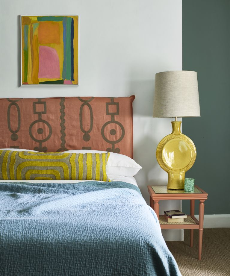colorful bedroom with pink embroidered headboard and yellow bedside light, blue bedspread and colorful artwork