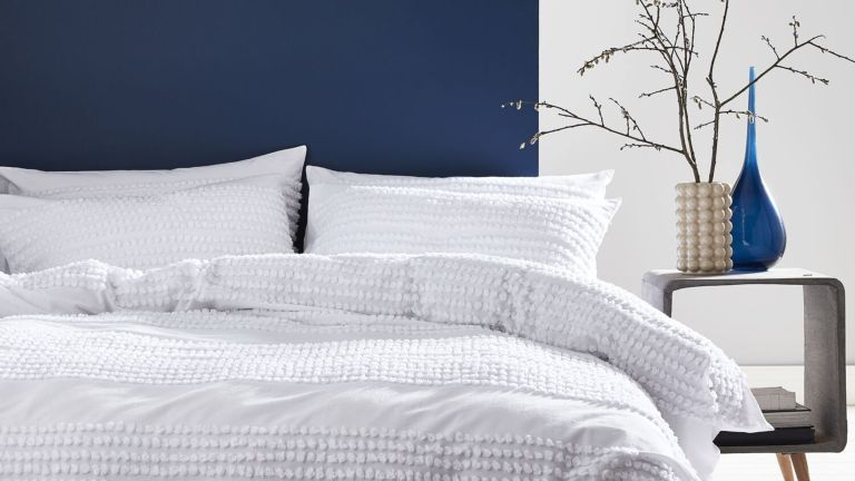A white textured duvet cover and pillowcases in a bedroom with a deep navy wall