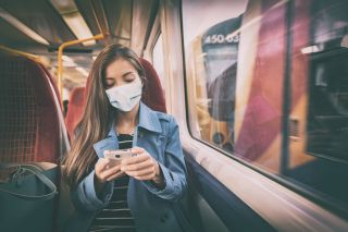 A person riding a train wearing a face mask.