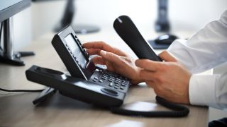 man using an office voip phone