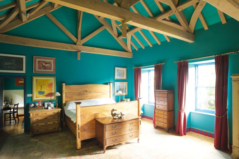 teal bedroom with beams and wooden furniture