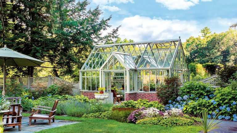 An example of the best food to grow in a greenhouse showing a large greenhouse surrounded by flowers and shrubbery next to an outdoor dining area