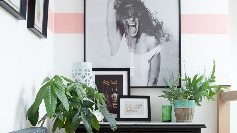 Debbie Goodwin: landing nook with console table, black and white photograph of woman, white walls with pink horizontal stripe paint effect