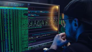 Best monitors for programming: Man looking at code on screen