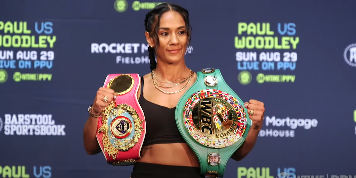 Amanda Serrano poses with her two belts at press conference for her boxing match with Yamileth Mercado