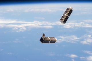 "Two of the 28 Dove cubesats that make up Planet Lab's ""Flock 1"" constellation are seen deploying into orbit from the International Space Station on Feb. 11, 2014."
