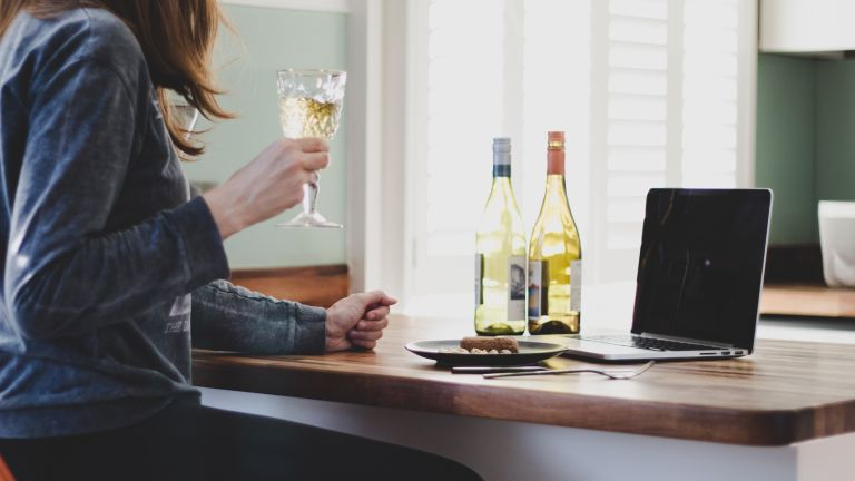 Woman drinking wine in front of a laptop