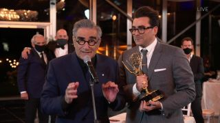 Dan Levy looks on as his father Eugene Levy delivers his part of their acceptance speech at the 72nd Emmys.