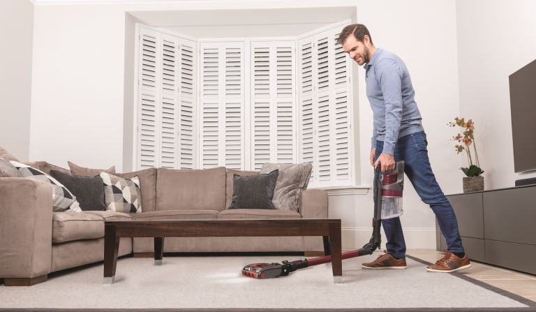 Man vacuuming under furniture with the Shark Anti Hair Wrap & DuoClean IZ201UK cordless vacuum cleaner