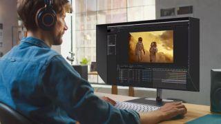 4K vs 8K: Man using ViewSonic VP3286 8K monitor to edit video