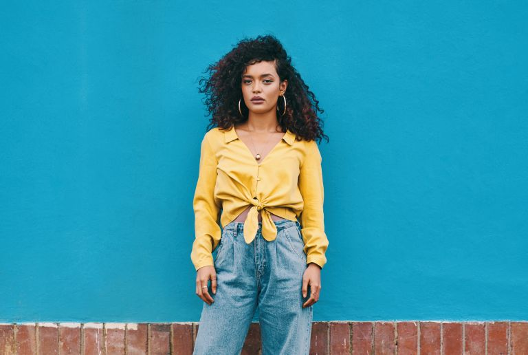 woman wearing jeans and a yellow top against a blue walll