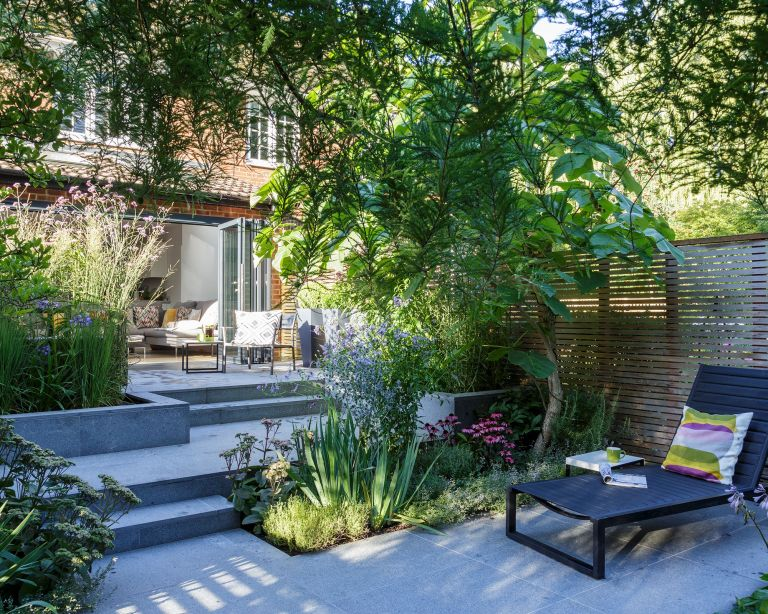 Small garden ideas with a stone patio and steps surrounded by green leafy vegetation and a wooden fence.