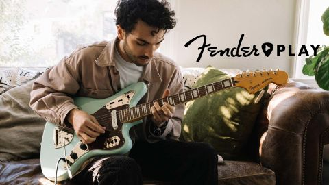 Fender Play review: Man plays an electric guitar sat on the couch