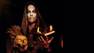 A press shot of Nergal from Behemoth holding a skull and a candle