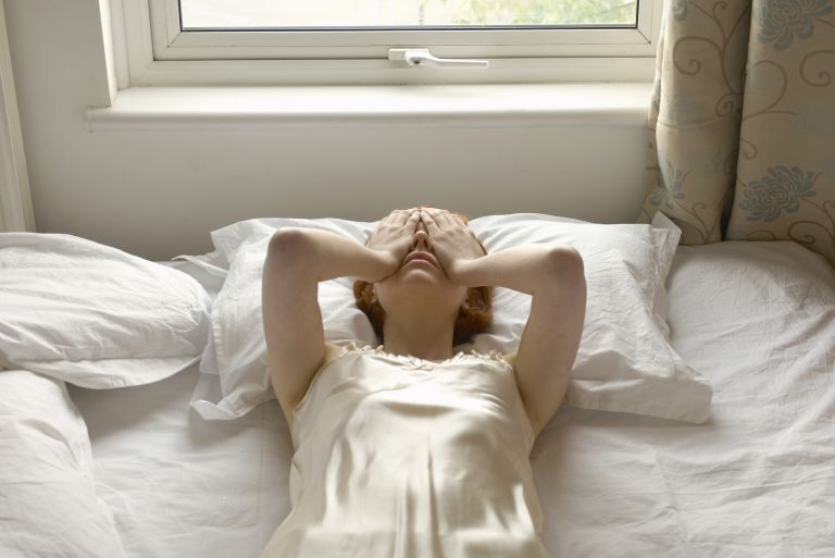 woman lays in bed with her hands over her eyes