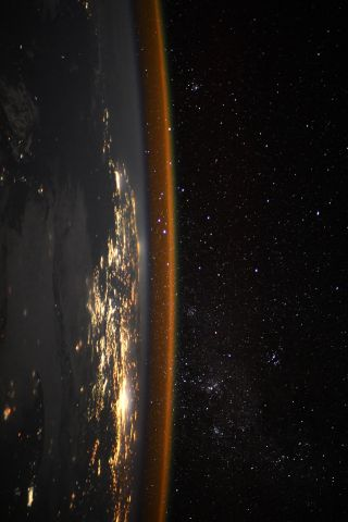 The sideways Earth glimmers in this photo taken from the International Space Station