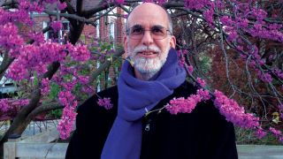 Cuneiform Records' Steve Feigenbaum poses against some pink blossom