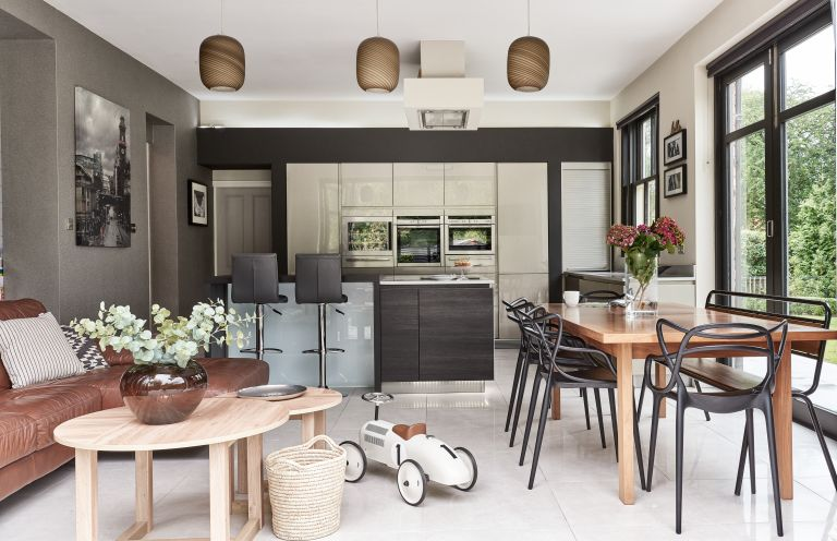 Open-plan kitchen diner with dining table, sofa and bi-fold doors