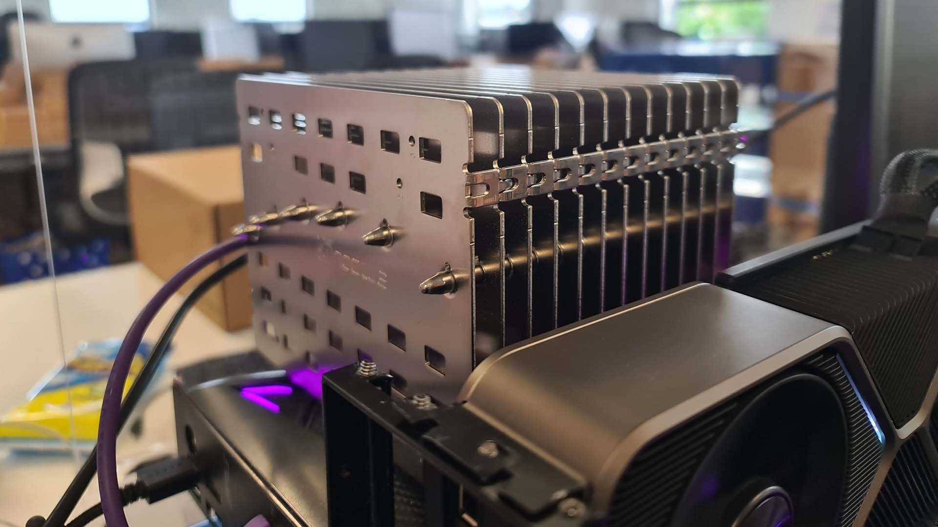 The Noctua NH-P1 air cooler mounted on an open-bed test bench with pink RGB lighting