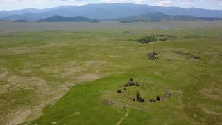 Here, an aerial view of the burial mound in southern Siberia. A distinct circle can be seen on one plane.